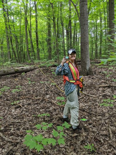 Fahrig's student Adrianne Hajdasz surveying birds using a small recorder that captures bird song.