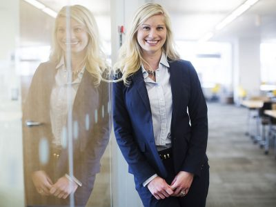 Angela Dionisi leans against a glass wall in an office and smiles for the camera.