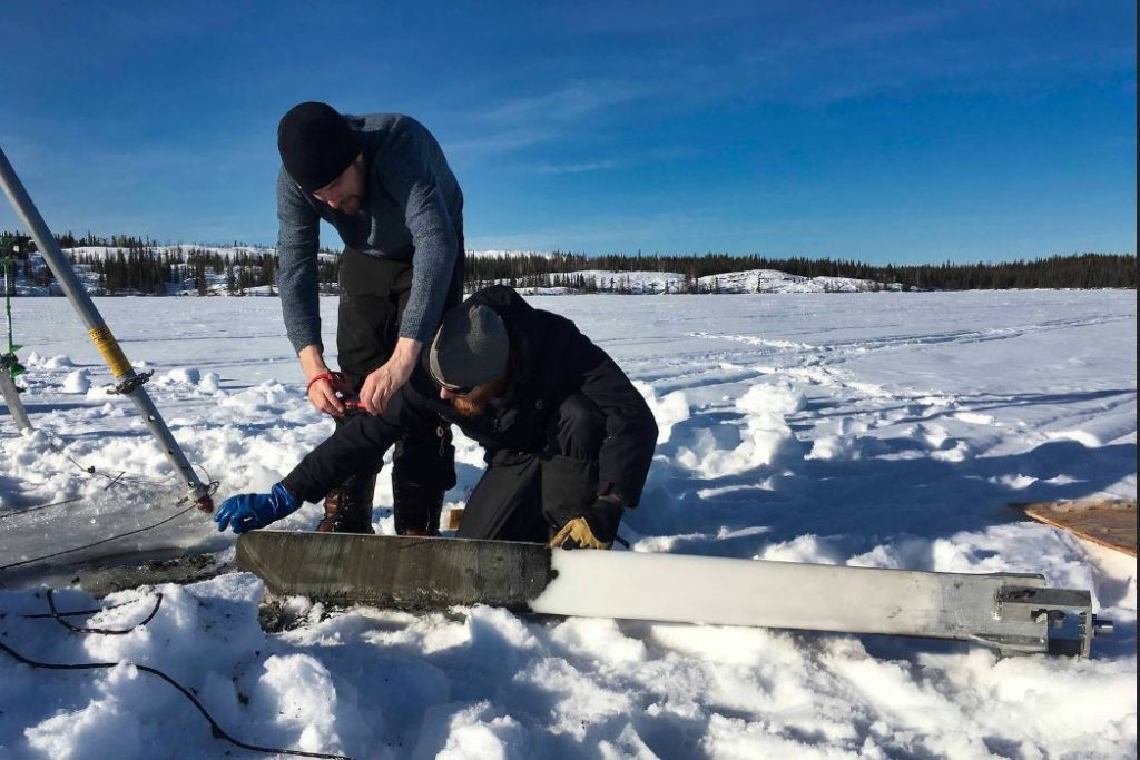 Two students inspect a frozen mud core on a lake in Yellowknife in March 2019