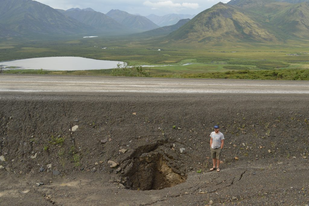 A student stands on the side of the Dempster highway in 2017 which shows cracks and gaping holes in the gravel and permafrost foundation of the roadway. damage.
