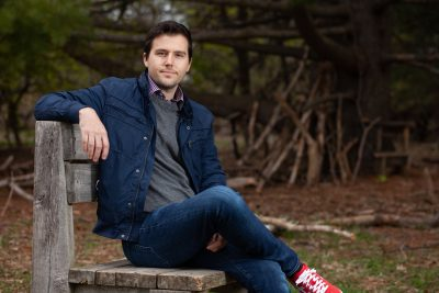 Heath MacMillan, Biology professor at Carleton University sitting on an outdoor wooden bench