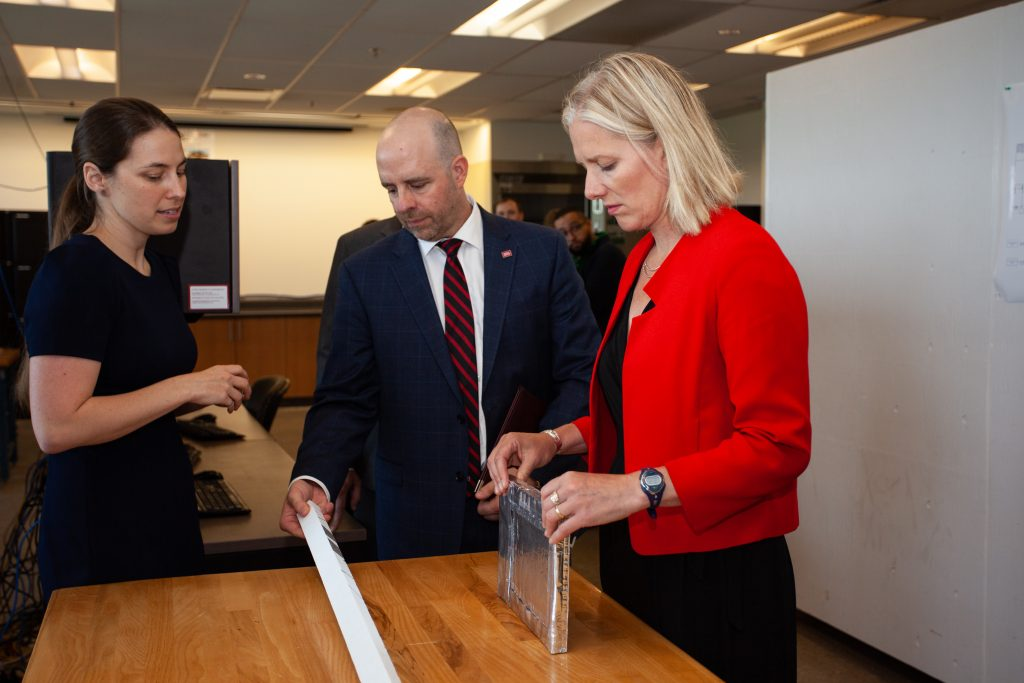 The Honourable Catherine McKenna, Minister of Environment and Climate Change looks at experimental materials used in the construction of building envelopes related to insulation. Professor Cynthia Cruickshank describes her work while Carleton president and vice-chancellor Benoit-Antoine Bacon looks on.