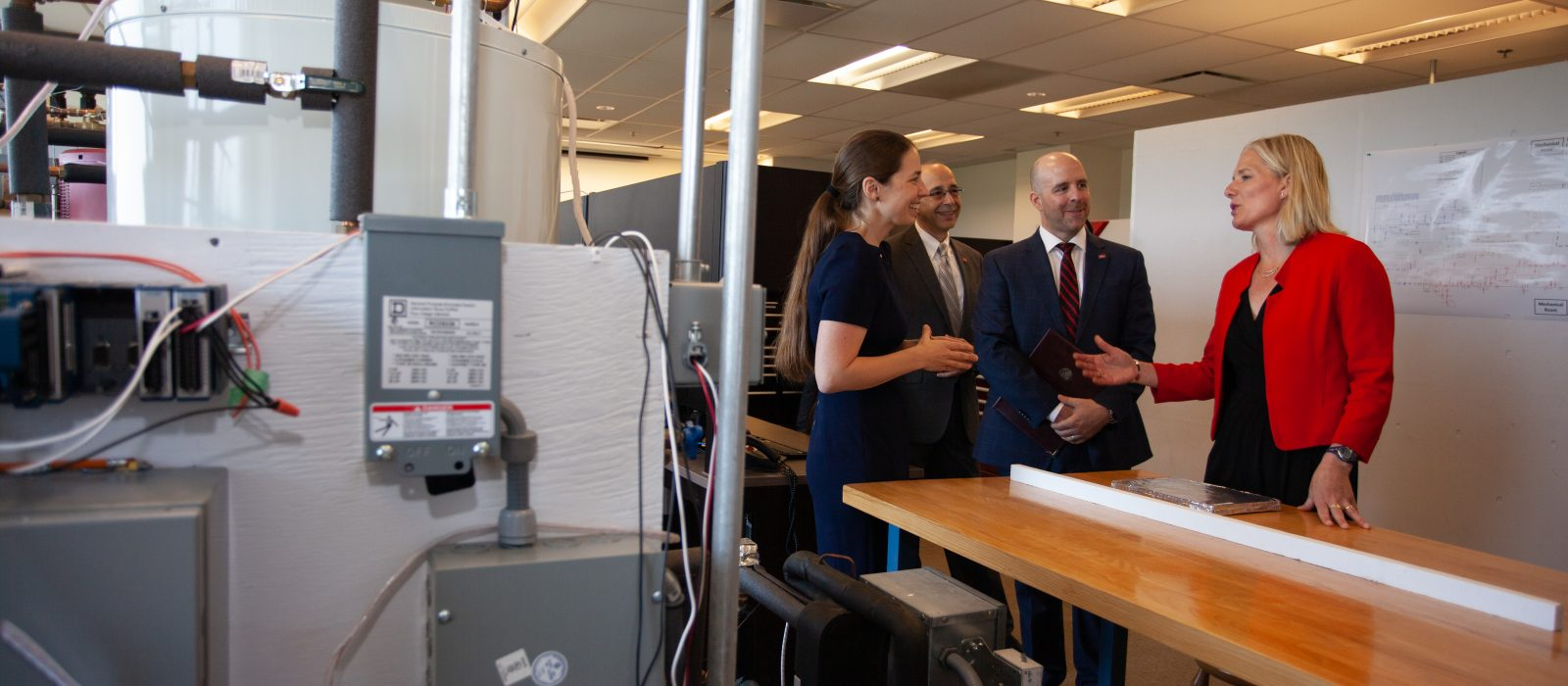 The Honourable Minister of Environment and Climate Change Catherine McKenna speaks with lead researcher Professor Cynthia Cruickshank, Carleton's Vice-President, Research and International Rafik Goubran, and Carleton's President and Vice-Chancellor Benoit-Antoine Bacon in a research lab setting.