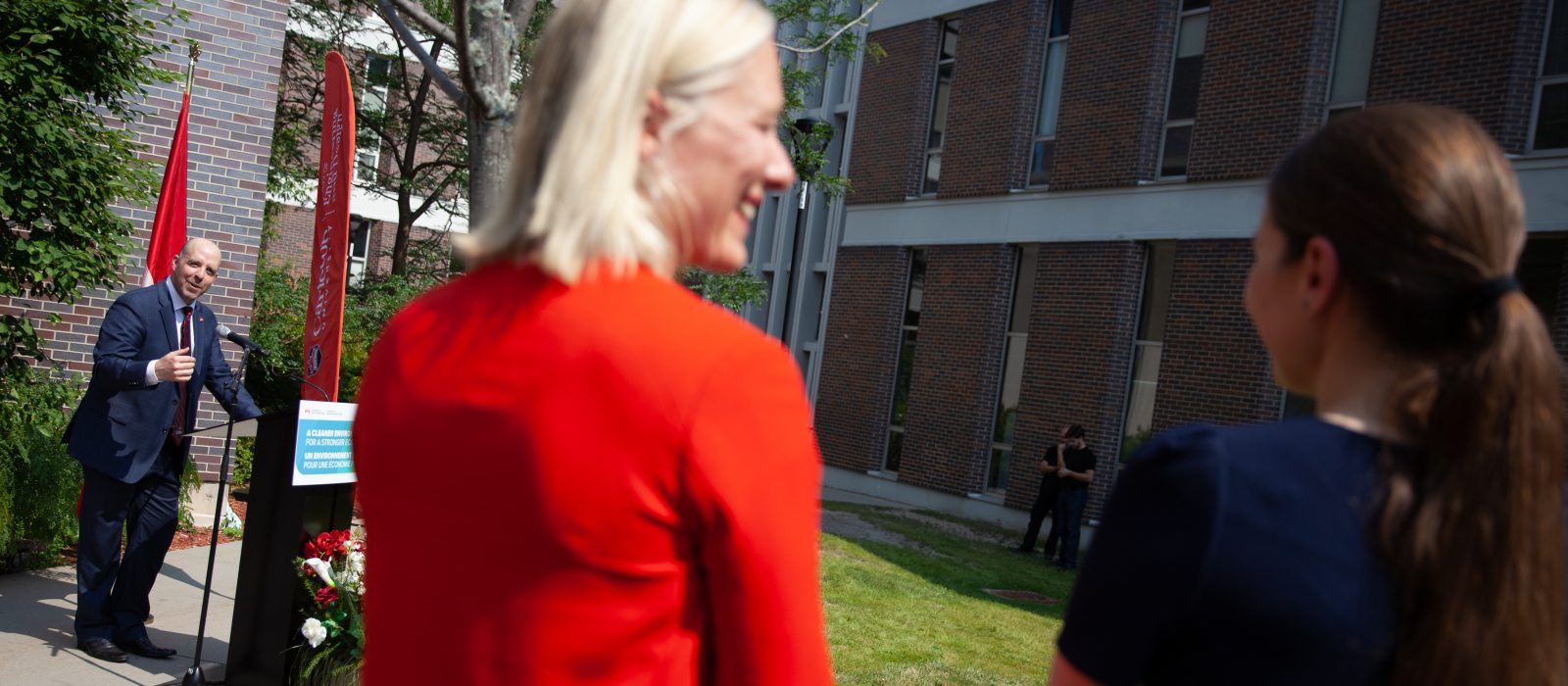 Carleton's President and Vice-Chancellor Benoit-Antoine Bacon stands outdoors at a podium and is smiling at Minister McKenna and Professor Cynthia Cruickshank