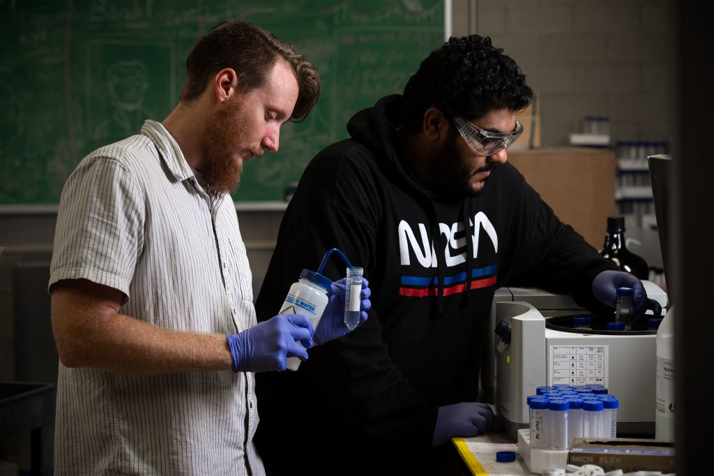 Braden Gregory and Nawaf Nasser employ a centrifuge in their sediment research.