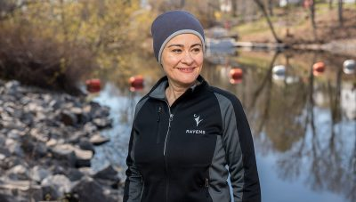 Banu Ormeci stands at the water's edge wearing a light jacket and toque.