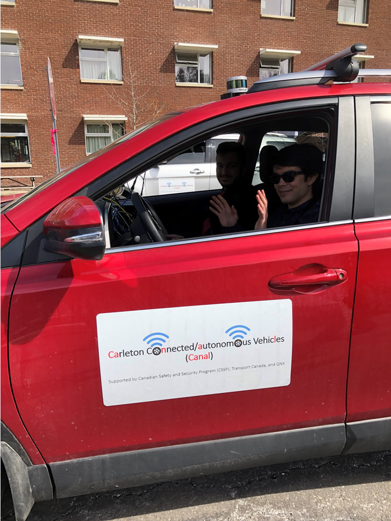 two passengers in a red autonomous vehicle car, the driver has his hands off the wheel