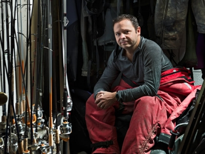 Steve Cooke in hip waders sitting in the storage room full of fishing poles